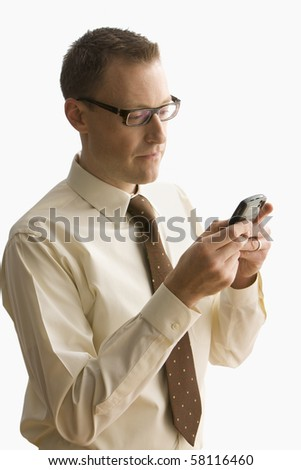 A businessman is holding a cell phone and writing a text message.  Vertical shot.  Isolated on white.
