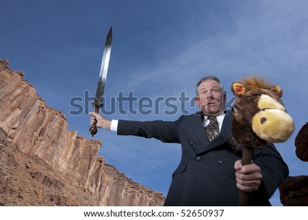 A businessman is holding a sword in an attack posture while riding a stick pony in a desert setting. Horizontal shot. - stock photo