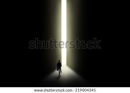 A businessman is holding briefcase and walking towards an open door with light - stock photo