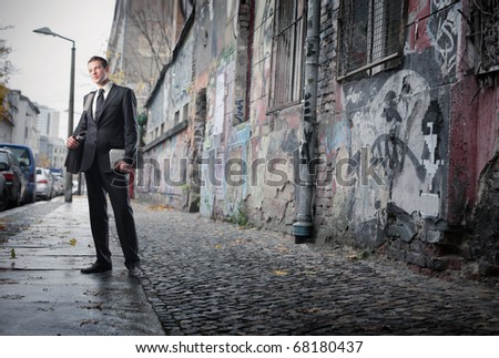 A businessman is looking around in a poor neighborhood - stock photo