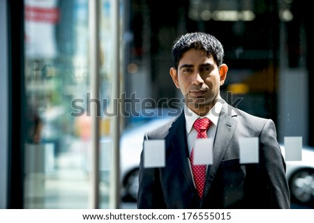A businessman is looking outside the glass door. - stock photo