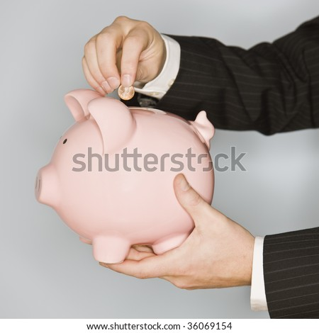 A businessman is putting a coin in the slot of a piggy bank.  Square framed shot. - stock photo