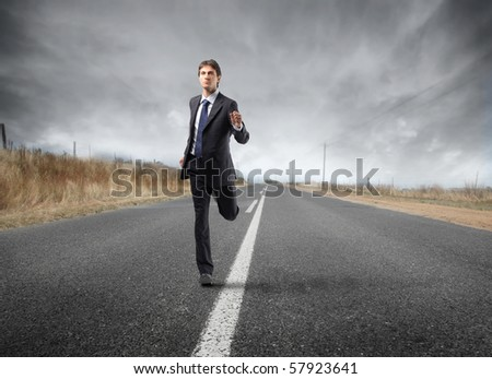 A businessman is running on the road - stock photo