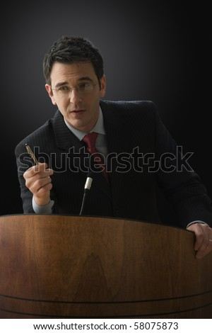 A businessman is standing at a lectern with a microphone giving a lecture. He has a pen in his hand and is gesturing with it. Vertical shot. - stock photo