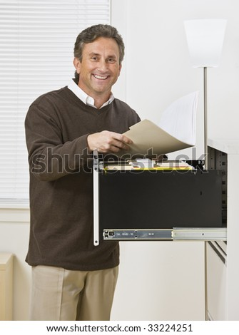 A businessman is standing in front of a filing cabinet and is smiling at the camera.  Vertically framed shot.