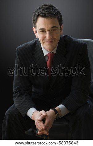 A businessman is wearing glasses and smiling while sitting and looking confident. Vertical shot.