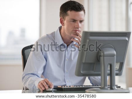 A businessman is working on a computer.  He is looking at the screen.  Horizontally framed shot.