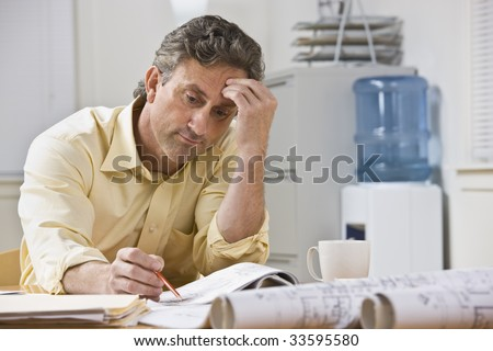 A businessman is working on blueprints in his office.  He is looking away from the camera.  Horizontally framed shot.