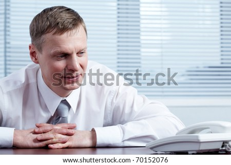 A businessman looking at telephone in suspense