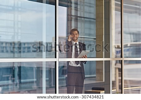 A businessman looking out the window while holding a tablet - stock photo
