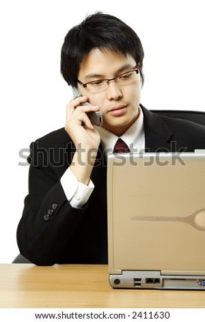 A businessman making a phone call and working on his laptop - stock photo