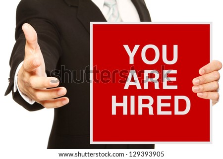 A businessman offering a handshake and holding a recruitment signboard - stock photo
