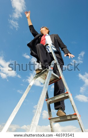 A businessman on a ladder reaching for the sky as if the limit is beyond the sky. - stock photo