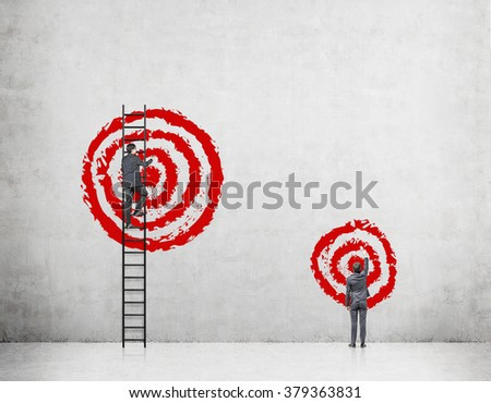 A businessman on a ledder painting a big red target, the other one standing on the floor painting a smaller target. Concrete background. Back view. Concept of goal-setting. - stock photo