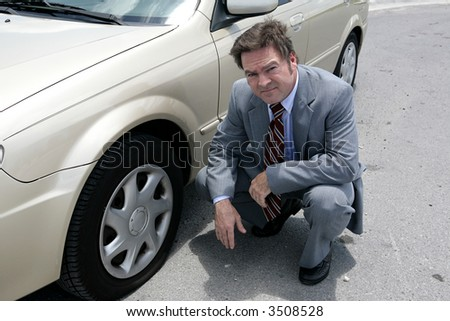 A businessman on the road with a flat tire.  He looks upset. - stock photo