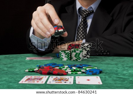 A businessman placing a bet in a Texas hold 'em poker game. - stock photo