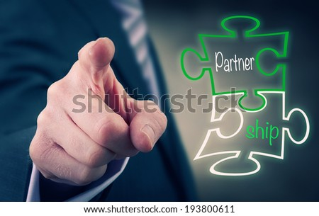 A businessman Pointing at a Partnership Puzzle Concept. - stock photo