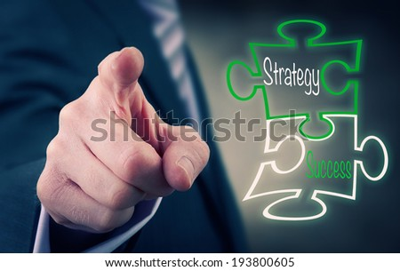 A Businessman pointing at a strategy success puzzle concept. - stock photo