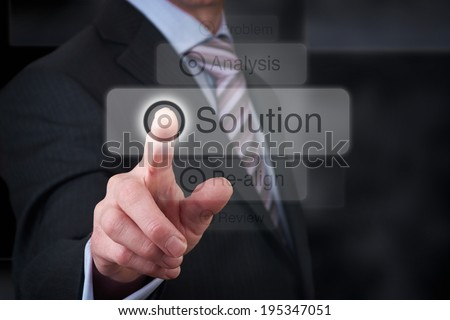 A businessman Pointing to a solution button on a clear screen. - stock photo