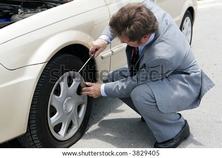 A businessman prying off the hubcap of his flat tire. - stock photo