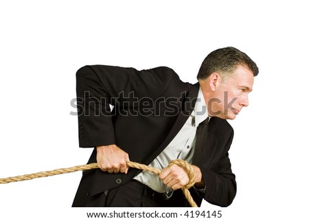 A businessman pulling on a rope as if dragging or struggling against something. - stock photo