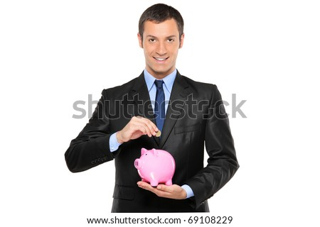 A businessman putting a coin into a piggy bank isolated on white background - stock photo