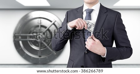 A businessman putting a one-hundred dollar banknote into the chest pocket. Safe at the background. Front view, no head. Concept of getting money. - stock photo