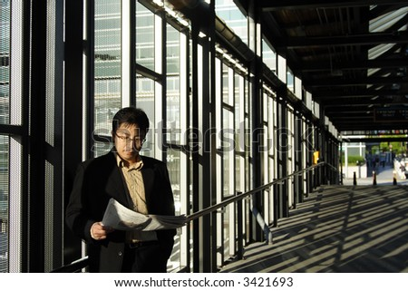 A businessman reading a financial newspaper at the train station