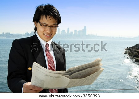 A businessman reading a financial newspaper on the beach