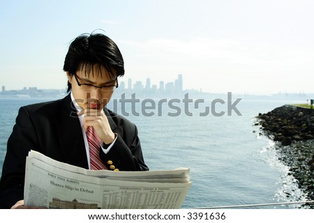 A businessman reading a financial newspaper outdoor - stock photo