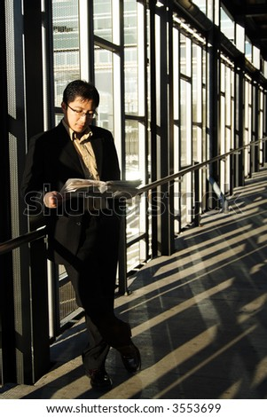 A businessman reading a newspaper in a train station