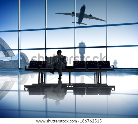 A Businessman Reading the Newspaper While Waiting for His Flight - stock photo