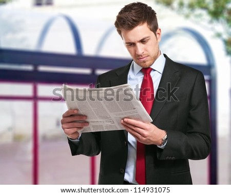 A businessman reads the finance newspaper while waiting for bus - stock photo