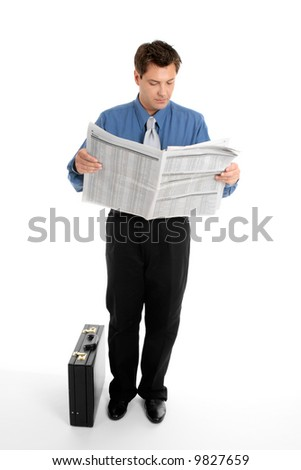A businessman reads the finance newspaper while waiting for bus, train, taxi.  Newsprint has been blurred. - stock photo