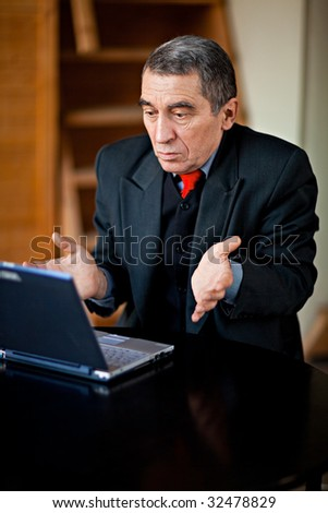 A businessman recoils from his laptop computer in horror. - stock photo