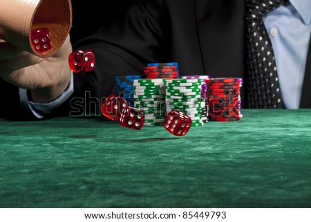 A businessman rolling the dice in a gambling game. - stock photo