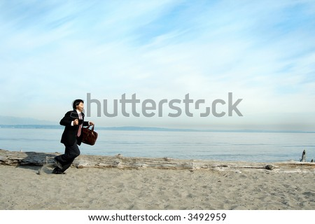 A businessman running on the beach carrying a cup and a bag