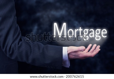 A businessman's hand holding the word, Mortgage. - stock photo
