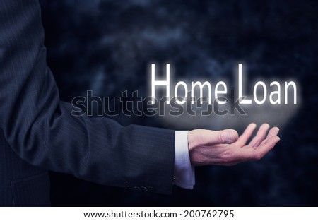 A businessman's hand holding the words, Home Loan. - stock photo