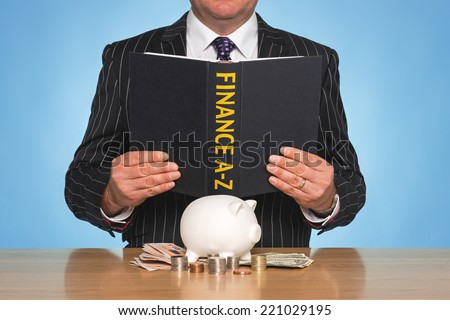 A businessman sat at a desk reading a FINANCE A-Z book - stock photo