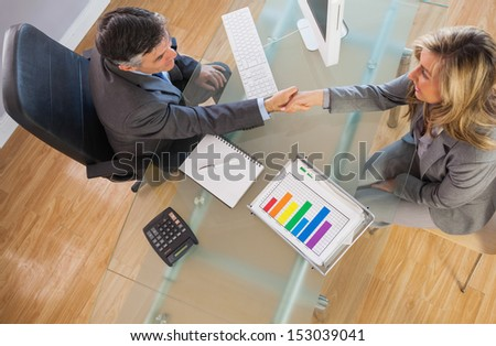 A businessman shaking the hand of a businesswoman above a desk in an office