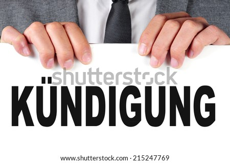 a businessman showing a signboard with the word kundigung, dismissal in german, written in it - stock photo