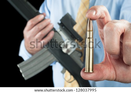 A businessman shows a large 223 bullet for his automatic assault rifle. - stock photo