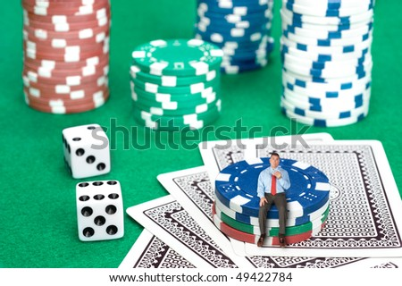 A businessman sits on a stack of poker chips in a conceptual image of business risk, chance and desperation.