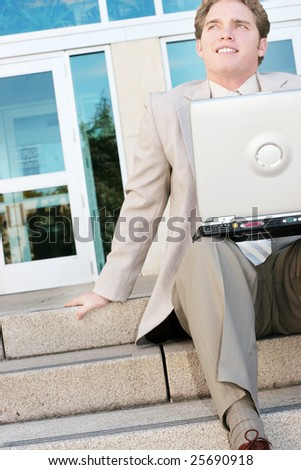 A businessman sits on the steps of a business building with his laptop thinking and wondering - stock photo
