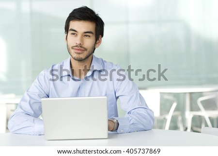 A businessman sitting at a desk, typing at a laptop, thinking