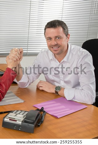A Businessman sitting at desk in bright office