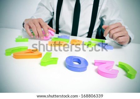 a businessman sitting in a desk forming the number 2014, as the new year - stock photo