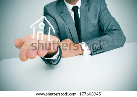 a businessman sitting in a desk showing a drawing of a house in his hand - stock photo