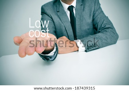 a businessman sitting in a desk showing the text low cost in his hand - stock photo